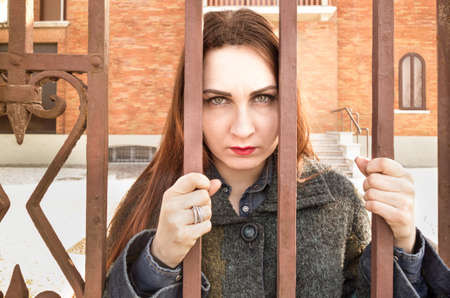 malaise: Sad depressed woman behind bars in mental hospitl sanatorium - Concept of psychological malaise and recovery structures Stock Photo