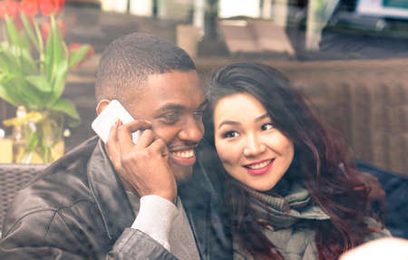 asian afro: Multiracial couple on date view through cafe window - Afro american man using phone and asian girlfriend facial expression in love - Cheerful mixed race friends - Closeup from glass focus on male
