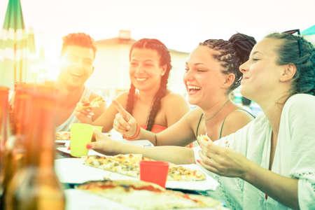 Amigos que se divierten comiendo pizza al atardecer en el restaurante bar de la playa - Adolescentes alegres que ríen en la fiesta de la cena de vacaciones de verano - Concepto de comida regocijo, desaturados mirada filtro de la vendimia Foto de archivo - 62361845