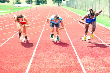 Runners at start grid front view on red athletics track - Professional sprinters explosive speed training - Concept of preparation for sports events and  international competition - Focus on black guy