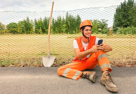 Worker road man having fun taking selfie with modern mobile phone - Portrait of young happy surveyor relaxing oudoor - Concept of hard work pause and modern technology - Smiling builder with helmet