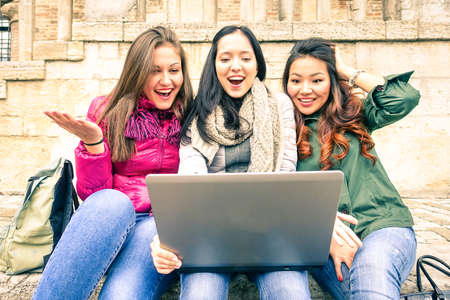 frienship: Young women having fun with laptop outdoor - Students looking at pc surprised - Three tourist girls sharing online photos of vacation with friends around world - Concept of frienship and technology