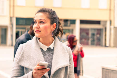 Young woman thinking face with mobile phone is standing on the street -  Portrait of thoughtful girl holding mobile - Concept of modern technology device and human moods - Tones of a cloudy bright day Stock Photo