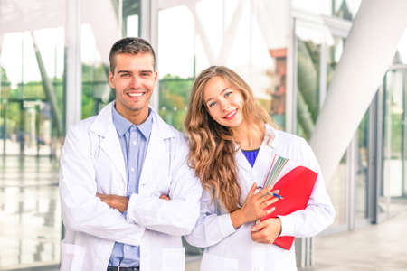 Medical students or dentists with white coat smiling at camera - Portrait of young doctor and  female assistant standing inside modern hospital - Concept of medicine dental and research professions Stock Photo