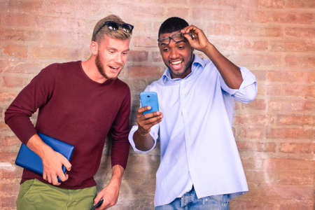 Surprised face friends looking phone screen - Afro american and caucasian students astonished facial expression by mobile on line special sale - Concept of amazing new technologies and lifestyle