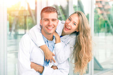 estudiantes medicina: Pares alegres de los estudiantes de medicina sonriendo a la cámara - El concepto de éxito positividad y logros en el estudio y en el mundo laboral - mirada de la vendimia de filtro suave con enfoque en la cara de la mujer joven