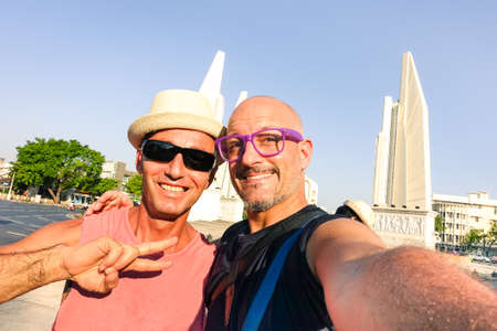 Happy couple of male friends taking selfie at Bangkok Democracy Monument - Cheerful tourists guys having fun with self photo in popular asian destination - Concept of joyful travel and old friendship Stock Photo