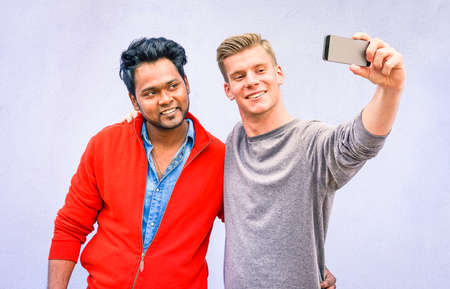 Black and white friends taking selfie on blue wall background - Happy men of different cultures united against racism - Multiracial young students self portrait - Concept of interracial friendship