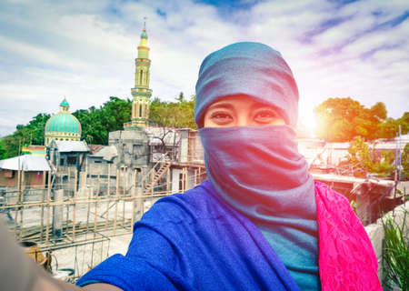 Beautiful muslim woman taking selfie in traditional islamic clothes - Young arabic girl fashion portrait at sunset with mosque and minaret background - Saudi arabian smiling female with covered face