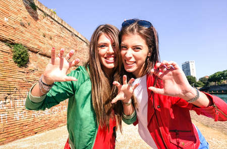 Cheerful best friend girls having fun roaring at photo camera outdoor - Young women  gesture and funny face expression - Concept of female friendship joyful moment during holiday travel in summer time Stock Photo