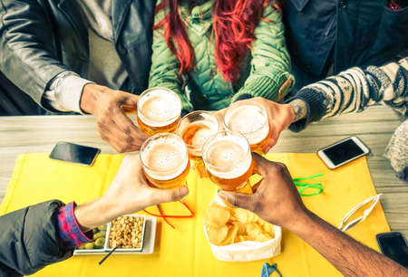 Group of friends cheers with beer cafe interior scene - Multiracial hands holding glasses of Pils in a toast to friendship and happiness -Teenager students gathering in restaurant -  Focus on glasses Stockfoto