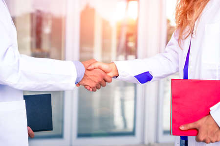 Doctors handshake with white coat holding folders at hospital room entrance - Physician professional business meeting inside clinic hand gesture close up - Concept of team working in medical world Stock Photo