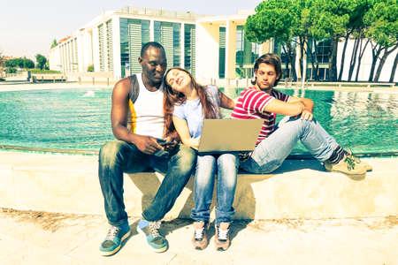 celos: amigos multirraciales con PC portátil al aire libre en la divertida escena de celos - hombre afroamericano y adolescentes amigos blanco, sentado con el ordenador cerca de la fuente - filtro de aspecto vintage en tonos pastel