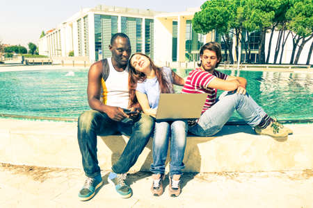 betray: Multiracial friends with pc laptop outdoors in funny jealousy scene - Afro american man and white teenagers friends sitting with computer near fountain - Vintage filter look with pastel tones Stock Photo