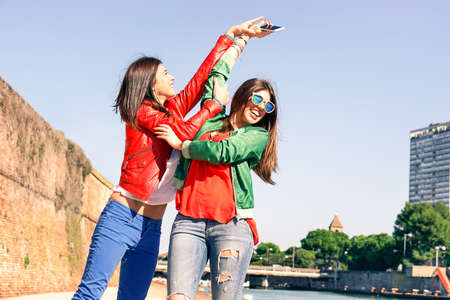 Young women playful girlfriends hands up holding mobile phone at pier - Cheerful female best friends playing as teenagers catching new smartphone each others - Concept of fun and teenage friendship