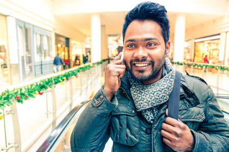 Young happy indian man making phone call smiling and wearing winter clothes - Handsome asian student using mobile having cheerful attitude - Concept of communication and successful lifestyle