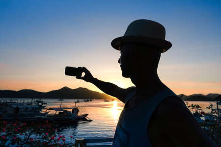 Man silhouette selfie at sunset with lagoon landscape at Philippines Island - Tourist  male taking self photo at sunrise lights - Concept of melancholy and sadness at the end of holiday Stock Photo