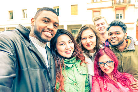 Multiracial group of friends taking selfie standing on the street at winter season - Happy students smiling at phone camera in a joyful self portrait - Concept of teenage cheerful moments together Stock Photo