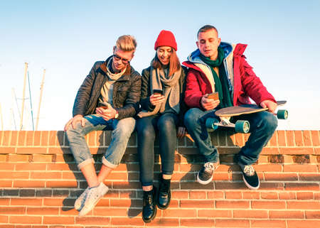 woman on phone: Group of friends using smartphone sitting on low briks wall - Young people addicted to mobile technology with disinterest talking each other - Teenagers holding telephone outdoor - Concept of leisure