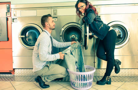 launderette: Young attractive couple doing laundry