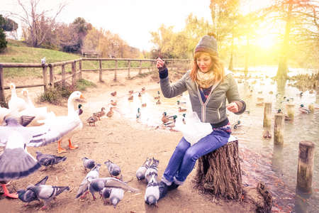 having fun in winter time: Young woman feeding ducks at the lake park before sunset - Girl in the winter time having fun with with animals by the river - Concept of outdoor life in the cold season - Backlit and sun halo filter Stock Photo