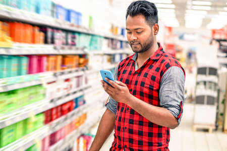 home store: Young indian man using mobile in blurred store lane - Handsome happy guy holding smart phone and smiling inside shopping mall next to colorful bottles - Radial zoom defocus on supermarket products Stock Photo