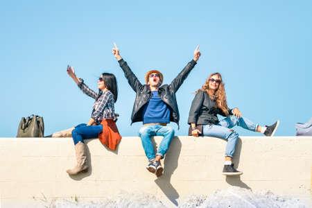 Exultant Freunde mit den Menschen die Hände hoch und glücklich Frau das Einfrieren der Moment nehmen selfie - Studenten Freude und Sieg Geste zusammen unter blauem Himmel im Hintergrund sitzen - Konzept der Menschen guten Emotionen