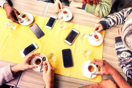 Top view friends hands drinking coffee espresso cup and mobile phones on table - Young multicultural people meeting at cafe bar indoor scene from above -  Winter concept of togetherness and technology Stock Photo