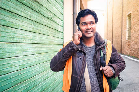 Young indian travel man making phone call walking on the street holding bag at winter time - Handsome bangladeshi guy looking up using mobile smiling outdoors  - Communication concept with copy space Stockfoto