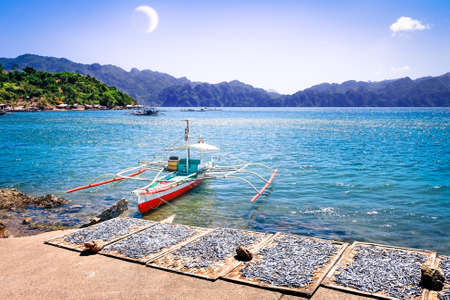 outrigger: Philippines Islands seascape with old outrigger boat and fresh drying fish on small harbor at Coron blue lagoon after sunset - Travel concept of nature panorama at nautical twilight time Stock Photo