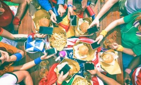 Barbeque supporters party around table holding phone - Top view of fast food lunch table with people using mobile as modern lifestyle and technology addiction concept - Vintage nostalgic filter look photo