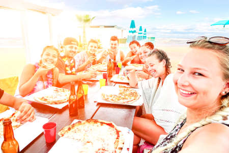 Big group of friends pizza party selfie on beach bar restaurant at sunset - Happy teenagers having fun on vacation at dinner with drinks and food on table - Sun halo filter focus on right third girl Stock Photo
