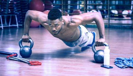 gritty: African american man doing push up workout in dark gym using kettlebell - Black gritty face guy working on chest muscles exercise at fitness center - Bluish vintage filter look with dim light effect Stock Photo