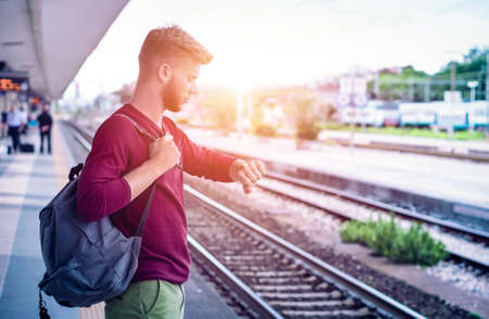 Young man checking the time on wristwatch at rail station platform - Student commuter waiting train at railway departures in pensive facial expression - Everyday lifestyle concept with sun halo filter