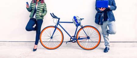 Couple de navetteurs avec vélo tenant téléphone mobile et ordinateur portable pc penchant sur le mur blanc urbain - Concept de la vie quotidienne va au travail ou à l'étude dans la ville et de l'utilisation de la technologie moderne photo