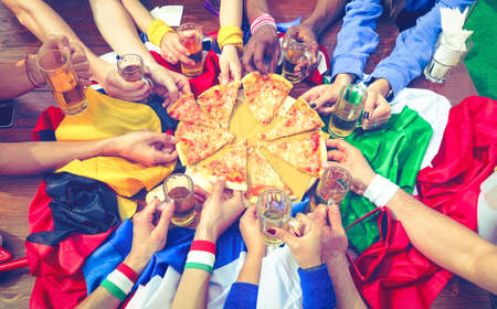 Multicultural friends eating pizza margherita top view - Group of multiracial people different hands sharing food at sport event party above image - Concept of friendship with vintage filter look photo