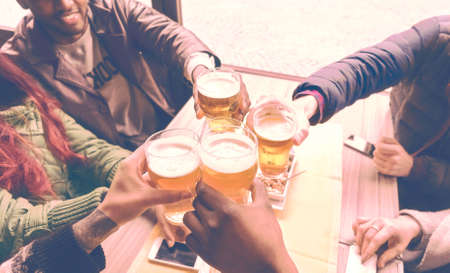 Friends cheering with beer glasses sitting around cafe bar table - Group of multiracial people toasting and clinking drinks at each others health inside pub photo