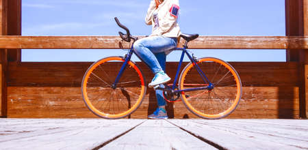 Two wheeler commuter standing on wooden footbridge with sport bike - Woman riding bicycle at summertime on sunny day cropped image of legs and cycle on urban bridge - Concept of wheels green transport