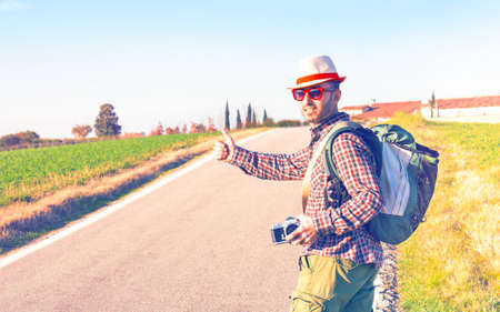 Traveler hitchhiker man thumb up walking on road - Middle age wanderer standing at county route on summer trip around world - Concept of cheap holidays with alternative ways to move - Vintage filter Stock Photo