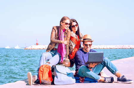 trotters: Happy best friends traveling on summer holiday are waiting ferry - Cheerful young travelers  using laptop while sitting by ocean at pier on sunny spring break day - Concept of share journey together Stock Photo