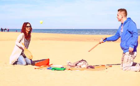 Couple jouant jeu de tennis de plage sur le sable avec l'océan bleu et fond de ciel - Ludique jeune famille amuser le week-end le jour de printemps ensoleillé - concept de moment joyeux et mode de vie actif photo