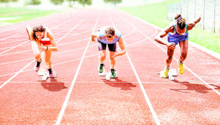 jamaican man: Row of multiracial runners at start grid on red athletics track - Professional sprinters explosive speed training - Concept of preparation for sports events and competition - Focus on black guy