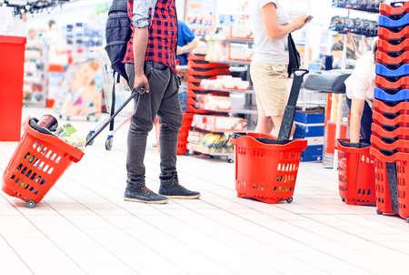 빨간색 쇼핑 트롤리를 들고 슈퍼마켓 결제에서 사람들 - 오른쪽 바구니에 초점을 맞춘 백화점 내 일상 생활의 개념
