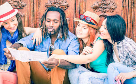 Group of multiracial happy friends looking map - Girlfriends on holiday asking direction at handsome dreads hair man sitting outdoor - Concept of girls on tour in the city - Main focus on male