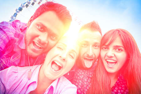 Group of best friends having fun taking selfie at ferris wheel at sunset - Multiracial friendship concept and new technologies - Desaturated vintage filter look with backlight