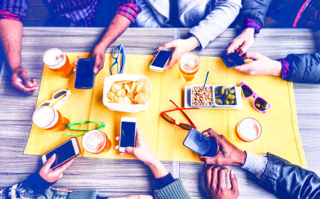Group of friends texting phone message inside pub top view image - Multicultural teenagers social network addicted together around table with pints of beer and snacks photo