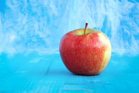 Red apple fuji on abstract  blue sky color background  - Isolated healthy organic fruit  front view on aquamarine wood with copy space