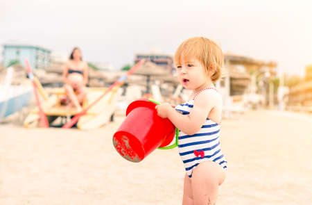 Toddler standing on the beach holding red bucket - Little girl playing on the beach at sunset with mother at background looking after her - Concept of children safety with dramatic vintage filter look