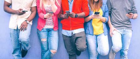 Adolescentes mensajes de texto mensajes de teléfono móvil apoyándose en la pared urbana - Grupo de amigos multirraciales utilizando pie celular al aire libre - Concepto de adicción a los estudiantes a la red social y la tecnología telefónica Foto de archivo - 85859427