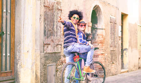 Interracial couple of tourists on bike tour turning pointing finger at old city alley view - Happy traveler friends riding bicycle looking around ancient european streets - Alternative tourism concept